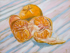 two blood oranges sit on a white linen cloth