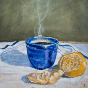 Coffee steams in a porcelain cup sitting on a white table cloth beside a peeled mandarin orange.