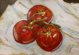 Two tomatoes on a white cloth