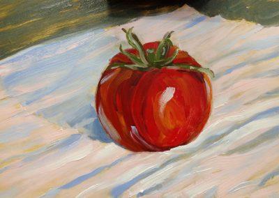 A single tomato on white cloth