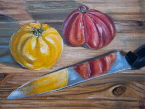 A yellow and a red tomato sit on a cutting board beside a kitchen knife which reflects them.